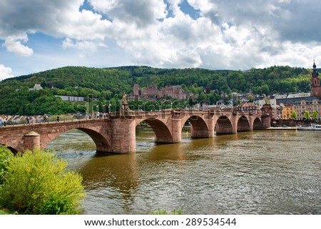 Old Bridge Over Neckar River with View of Old Town Heidelberg, Baden-Wurttemberg, Germany Nestled in Lush Green Foothills on River Bank - stock photo