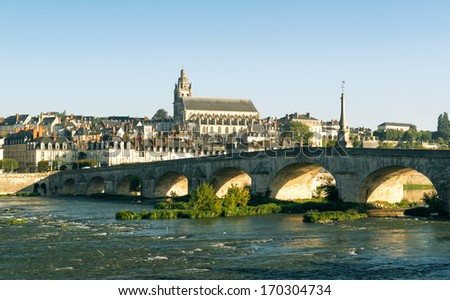 Old bridge over the Loire in Blois, France. Cathedral of Blois in the background. - stock photo