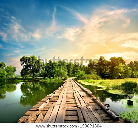 Old bridge over the river in the countryside - stock photo