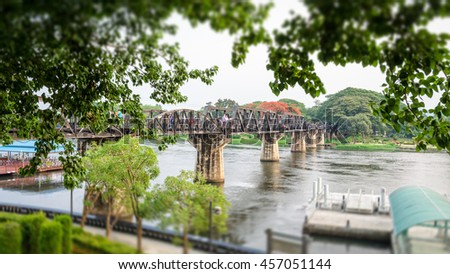 Old bridge over the River Kwai on tilt shift is a historical attractions during World War 2 the famous of Kanchanaburi Province in Thailand,16:9 wide screen - stock photo