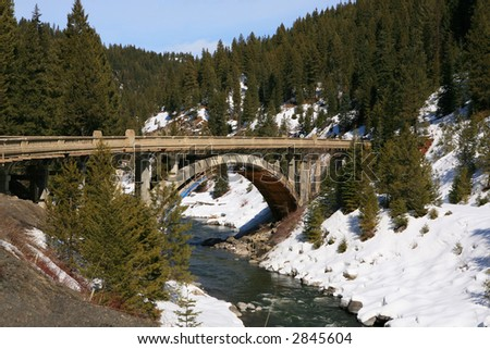 Old bridge over the river with snow