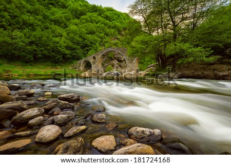Old bridge through river with fast stream - stock photo
