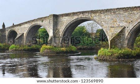 Old bridge with arches, turrets and buttresses crosses the Forth in Stirling, Scotland, scene of the historic Battle of Stirling Bridge where Scots led by William Wallace defeated the English in 1297. - stock photo