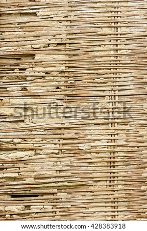 old broken bamboo lath and plaster wall in rural Thailand - stock photo