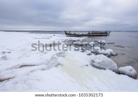 Old broken boat wreck and rocky beach in wintertime. Frozen sea, evening light and icy weather on shore like fairy tale country. Winter on coast. Blue sky, white snow, ice covers the land.