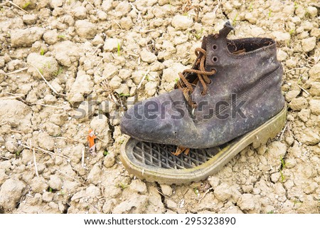 Old broken boot abandoned in the countryside - stock photo