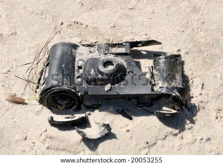 Old broken camera in the sand on the beach