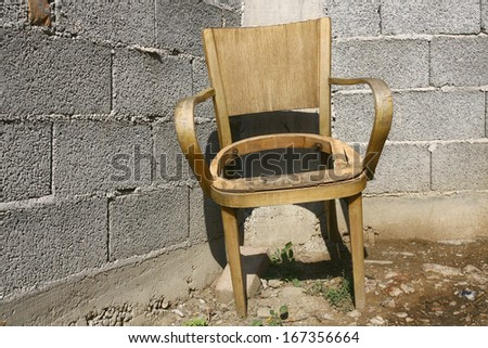 old broken chair near the old wall - stock photo