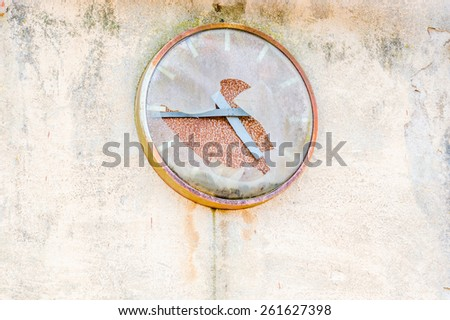Old broken clock on industrial wall. Cover is broken and time has stopped. Place for text beside clock. - stock photo