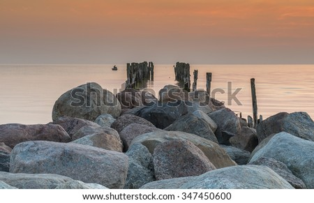 Old broken pier and fishing boat on horizon, Baltic Sea at dawn - stock photo