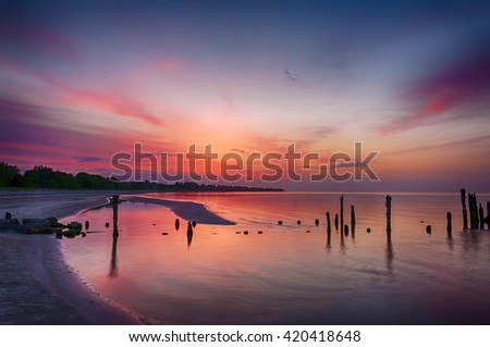 Old broken pier at sunset on the coast of the Baltic sea, Latvia - stock photo