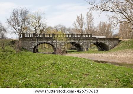 Old broken stone bridge. - stock photo