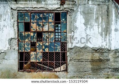 Old broken window in gray concrete wall - stock photo