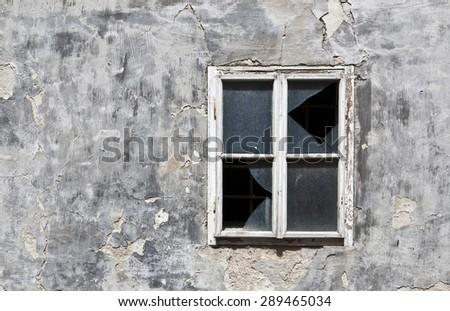 Old broken window part of decaying building - stock photo