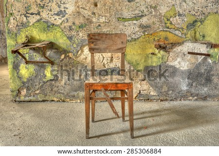 Old, broken, wooden chair against a filthy wall in an abandoned prison. Ready for interview or interrogation. - stock photo
