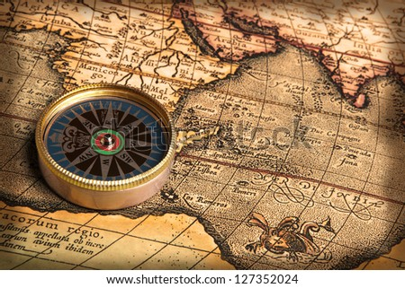 Old bronze compass on vintage map - stock photo