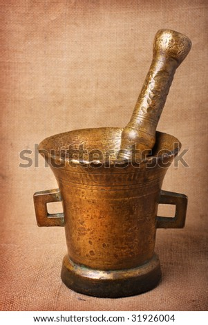 Old bronze mortar and pestle on sacking background