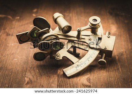 old bronze sextant on the wooden table  - stock photo