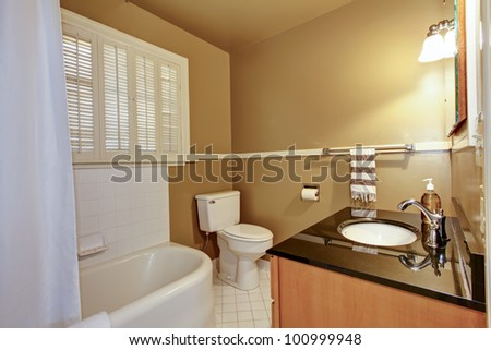 Old brown bathroom with white tub and modern sink. - stock photo