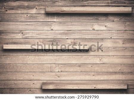 Old brown empty shelf on wooden wall - stock photo