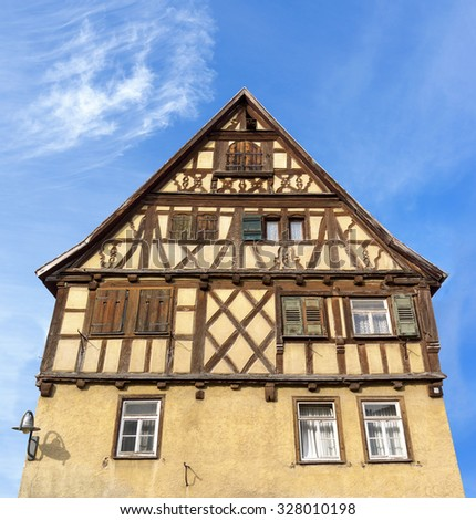 Old brown half-timbered house against a blue sky   - stock photo