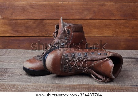 Old brown hiking boots on wooden background - stock photo