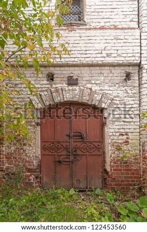 Old brown ornate metal double door in white brick wall. Gorodets, Nizhegorodsky region, Russia. Old brown ornate metal double door in white brick wall. Gorodets, Nizhegorodsky region, Russia.