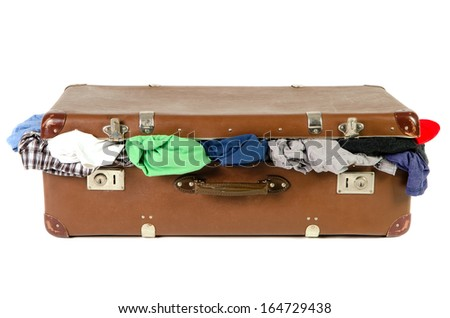 old brown suitcase full with clothes isolated before white background - stock photo