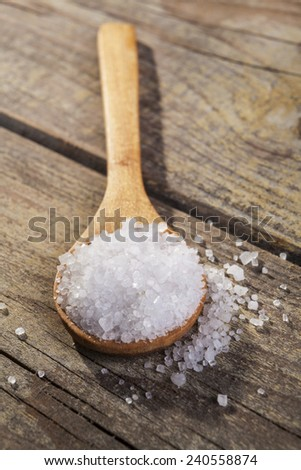 Old Brown wood spoon with salt crystals on wood table