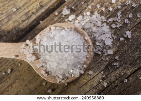 Old Brown wood spoon with salt crystals on wood table - stock photo