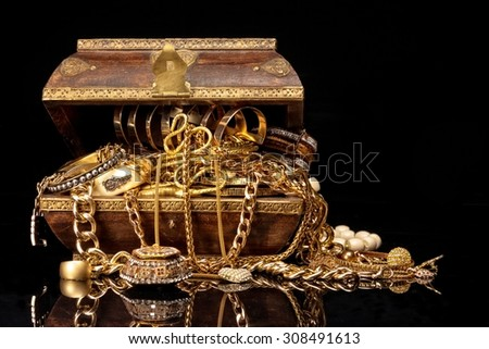 Old brown wooden chest with various golden jewelry, against black background.