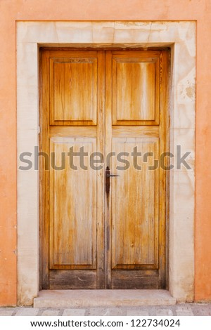 Old brown wooden door of a house entrance with an orange front