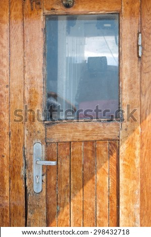 Old brown wooden door on the ship with a window