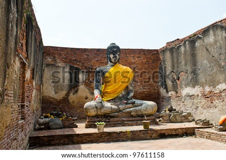 Old buddha statue and old wall with white sky, Thailand. - stock photo