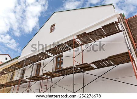 Old building facade with scaffolding under reconstruction  - stock photo