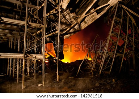 Old building in full flaming inferno, and a firefighter fighting the flames - stock photo