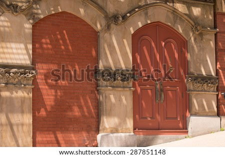 Old Building in Saint John New Brunswick (one door is bricked in and the other door is still use-able.  The shadows and light from the fire escape above cover the wall. - stock photo