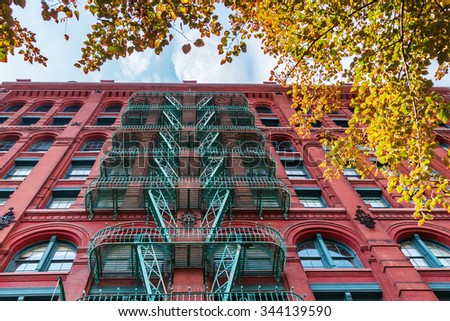 old building in Soho, Manhattan, NYC, with typical fire escape stairs  - stock photo