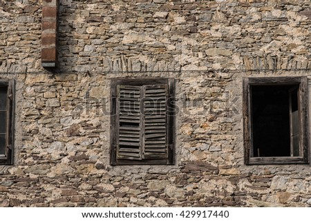 Old building wall with broken shutters open windows old brick and wood frames.  Northern Italy building in the Dolomites.