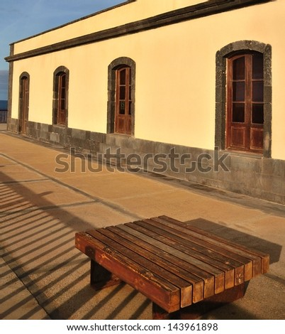 Old building with several windows and wooden bench, Jandia lighthouse, Fuerteventura - stock photo