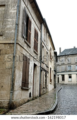 Old buildings and antique houses on quaint ancient cobblestone paved street in small French town in rural province of France (modern objects, signs, wires, antennas and sewer grates have been removed)