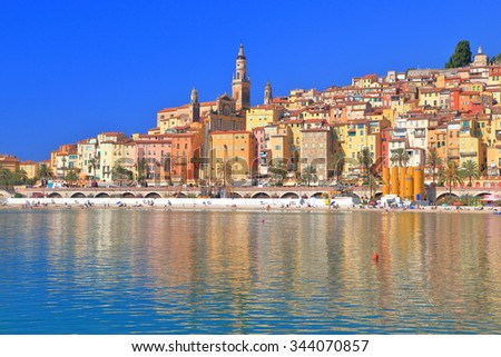Old buildings of the old town of Menton reflected by the calm sea, French Riviera, France
