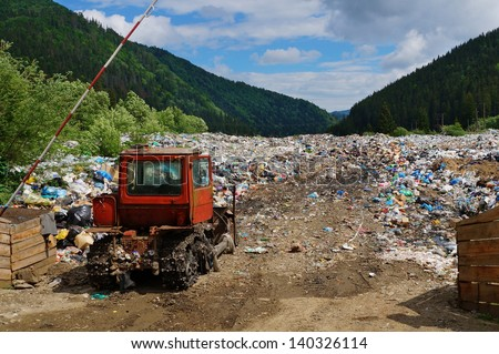 Old bulldozer at landfill entrance in mountains (nature pollution in Carpathian mountains, Ukraine) - stock photo