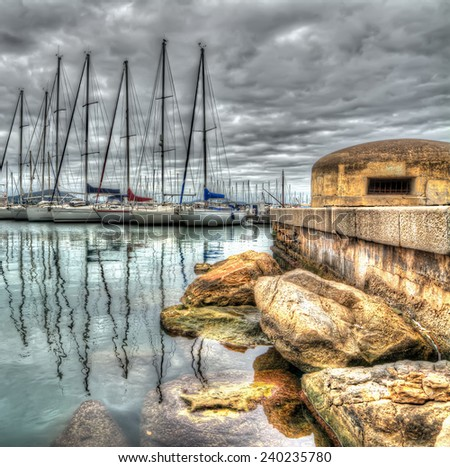 old bunker in Alghero harbor under a dramatic sky. Processed for hdr tone mapping effect - stock photo
