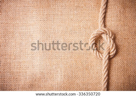 Old burlap and knot on a rope - stock photo