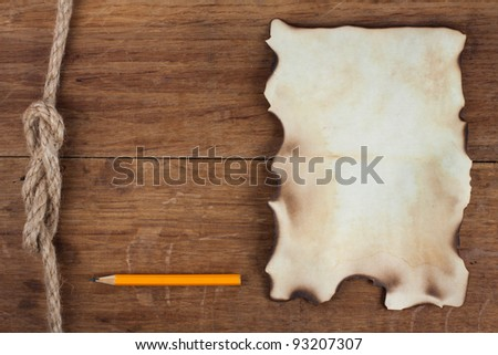 Old Burnt Paper and a Pencil on Wood background - stock photo