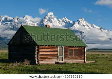 Old Cabin in Front of Grand Tetons - stock photo
