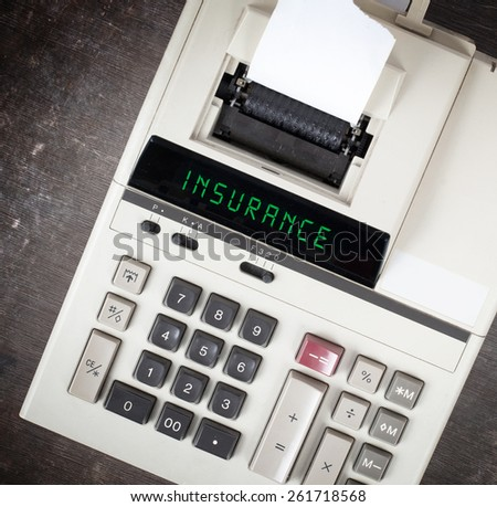 Old calculator showing a text on display - insurance - stock photo