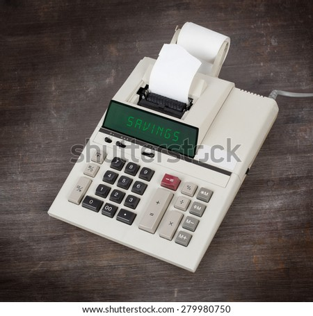 Old calculator showing a text on display - savings - stock photo