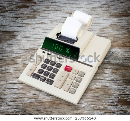 Old calculator with digital display showing a percentage - 100 percent - stock photo